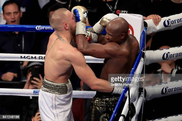 Conor McGregor and Floyd Mayweather Jr exchange blows during their super welterweight boxing match on August 26 2017 at TMobile Arena in Las Vegas...