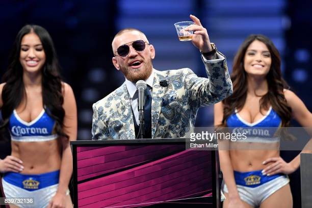 Conor McGregor holds up a cup of his Notoriousbranded Irish whiskey as he speaks during a news conference following his 10thround TKO loss to Floyd...