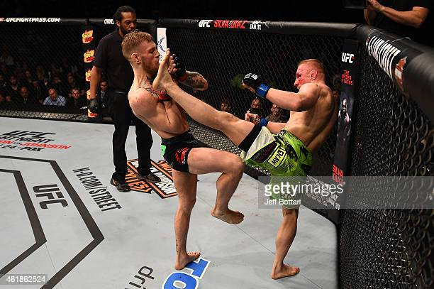 Conor McGregor of Ireland blocks a kick from Dennis Siver of Germany in their featherweight fight during the UFC Fight Night event at the TD Garden...