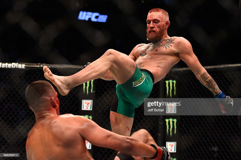 Conor McGregor of Ireland knocks down Nate Diaz in their welterweight bout during the UFC 202 event at TMobile Arena on August 20 2016 in Las Vegas...