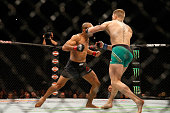 Conor McGregor of Ireland punches Jose Aldo of Brazil in their UFC welterweight championship bout during the UFC 194 event inside MGM Grand Garden...