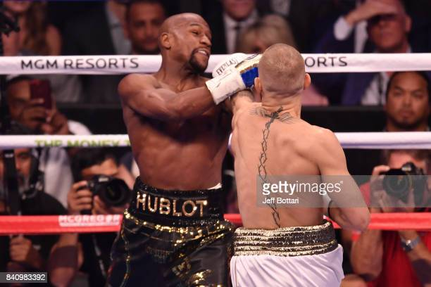 Conor McGregor punches Floyd Mayweather Jr in their super welterweight boxing match at TMobile Arena on August 26 2017 in Las Vegas Nevada Mayweather...