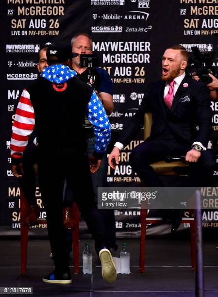 Conor McGregor reacts as Floyd Mayweather Jr walks past during the Floyd Mayweather Jr v Conor McGregor World Press Tour at Staples Center on July 11...