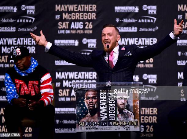 Conor McGregor speaks as Floyd Mayweather Jr waits in the background during the Floyd Mayweather Jr v Conor McGregor World Press Tour at Staples...