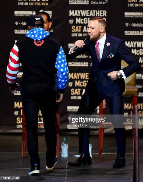Conor McGregor speaks as Floyd Mayweather Jr walks past during the Floyd Mayweather Jr v Conor McGregor World Press Tour at Staples Center on July 11...