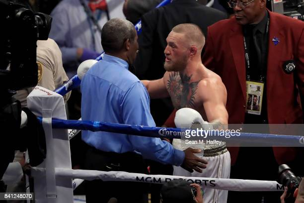 Conor McGregor speaks to referee Robert Byrd after losing to Floyd Mayweather Jr by 10th round TKO in their super welterweight boxing match on August...