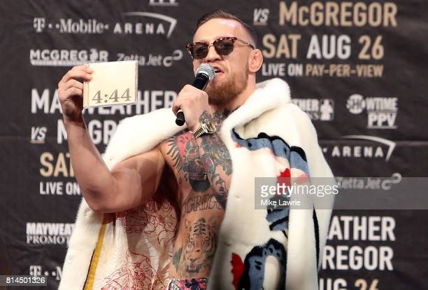 Conor McGregor speaks while holding up a JayZ '444' album during the Floyd Mayweather Jr v Conor McGregor World Press Tour event at Barclays Center...