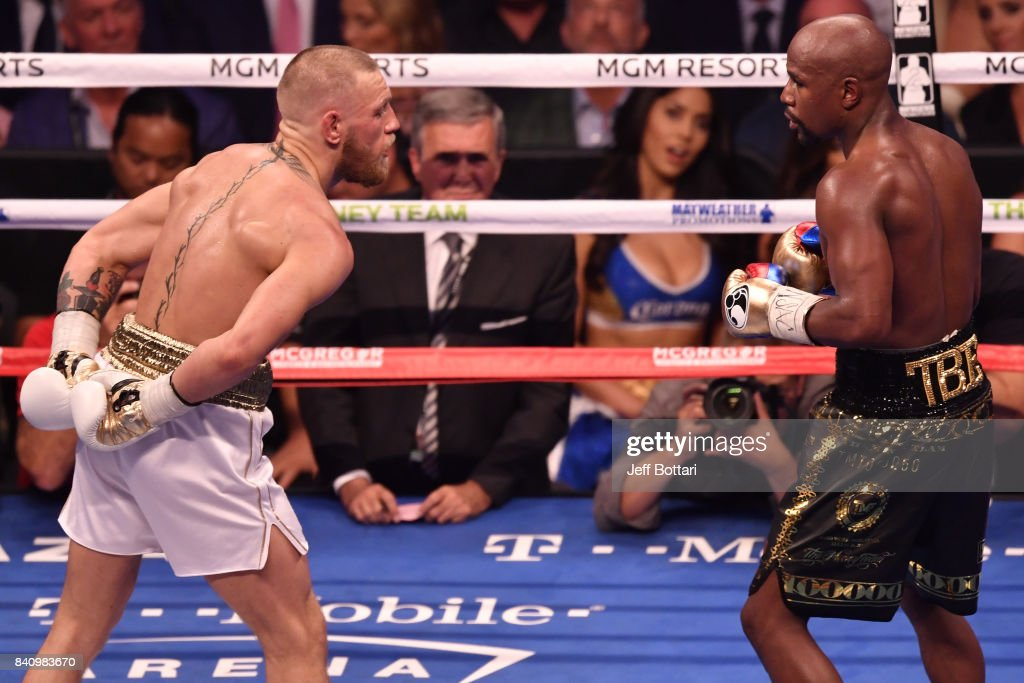 Conor McGregor taunts Floyd Mayweather Jr. by holding his hands behind his back in their super welterweight boxing match at T-Mobile Arena on August 26, 2017 in Las Vegas, Nevada. Mayweather won by 10th-round TKO.