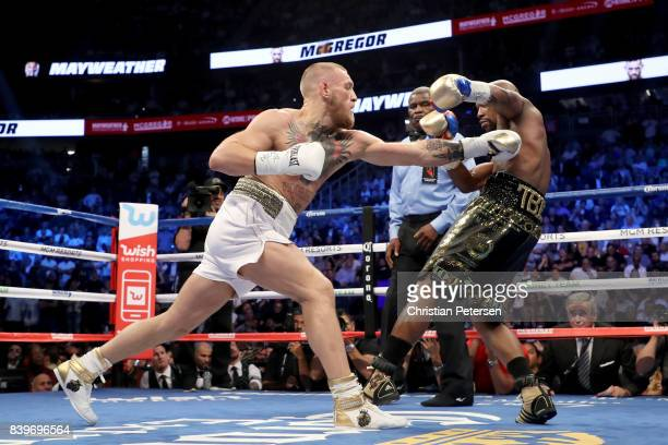 Conor McGregor throws a punch at Floyd Mayweather Jr during their super welterweight boxing match on August 26 2017 at TMobile Arena in Las Vegas...