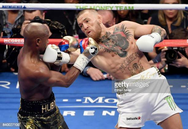 Conor McGregor throws a right at Floyd Mayweather Jr in the second round of their super welterweight boxing match at TMobile Arena on August 26 2017...