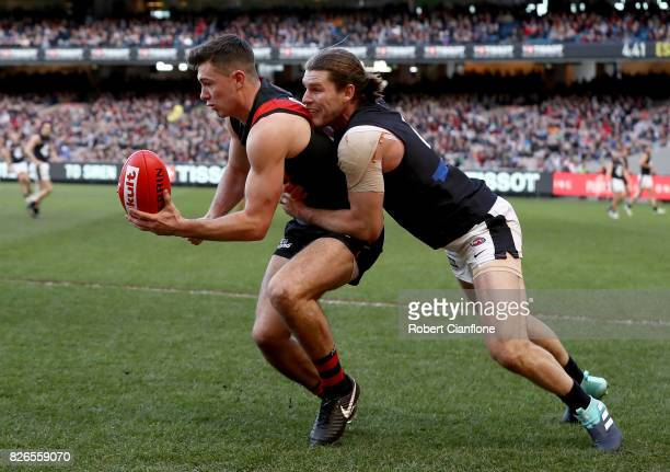 Conor McKenna of the Bombers is challenged by Bryce Gibbs of the Blues during the round 20 AFL match between the Essendon Bombers and the Carlton...