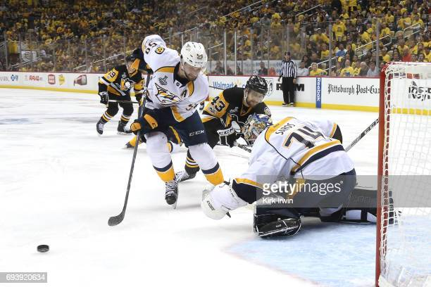 Conor Sheary of the Pittsburgh Penguins competes for the puck with Roman Josi of the Nashville Predators in front of goalie Juuse Saros in the second...
