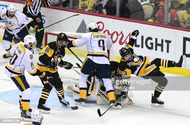Conor Sheary of the Pittsburgh Penguins falls at the net after colliding with Matt Murray and Filip Forsberg of the Nashville Predators in Game One...