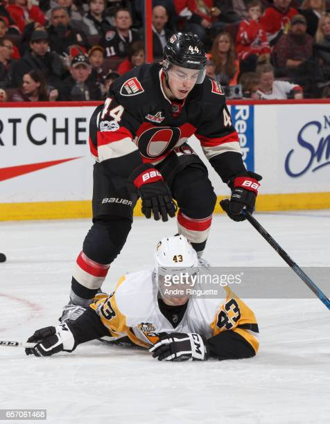Conor Sheary of the Pittsburgh Penguins falls to the ice after a puck battle with JeanGabriel Pageau of the Ottawa Senators at Canadian Tire Centre...