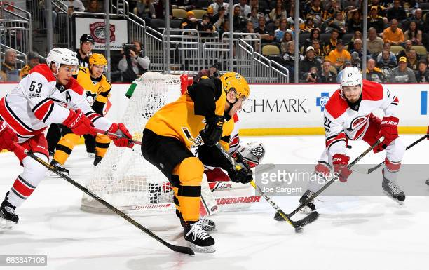 Conor Sheary of the Pittsburgh Penguins handles the puck in front of Brett Pesce and Jeff Skinner of the Carolina Hurricanes at PPG Paints Arena on...