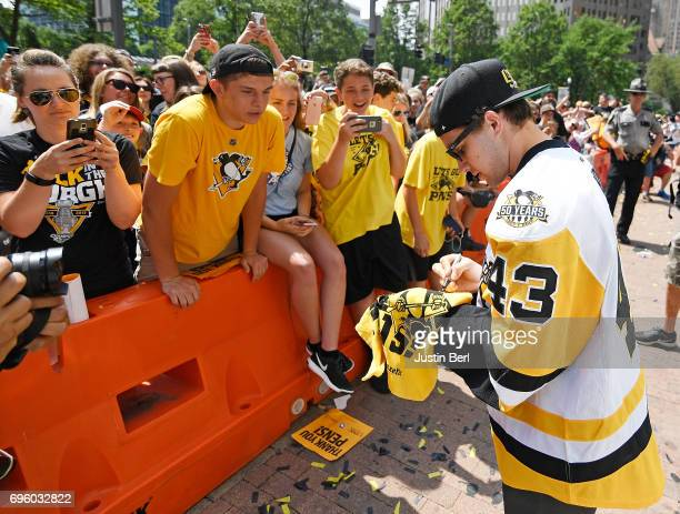 Conor Sheary of the Pittsburgh Penguins signs autographs for fans along the route during the Victory Parade and Rally on June 14 2017 in Pittsburgh...