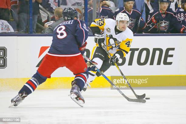 Conor Sheary of the Pittsburgh Penguins skates the puck past Zach Werenski of the Columbus Blue Jackets during Game Three of the Eastern Conference...