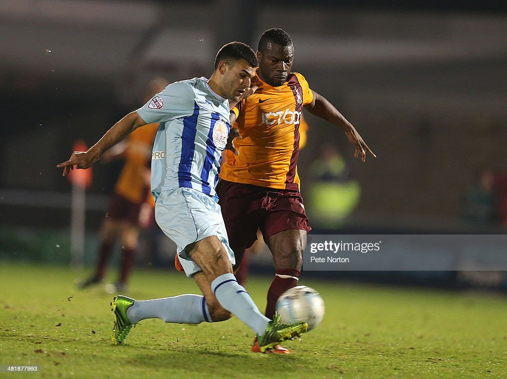 Conor Thomas of Coventry City plays the ball under pressure from Aaron McLean of Bradford City during the Sky Bet League One match between Coventry City and Bradford City at Sixfields Stadium on April 1, 2014 in Northampton, England.