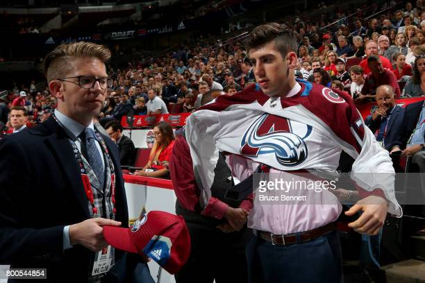 Conor Timmins puts on the Colorado Avalanche jersey after being selected 32nd overall during the 2017 NHL Draft at the United Center on June 24 2017...