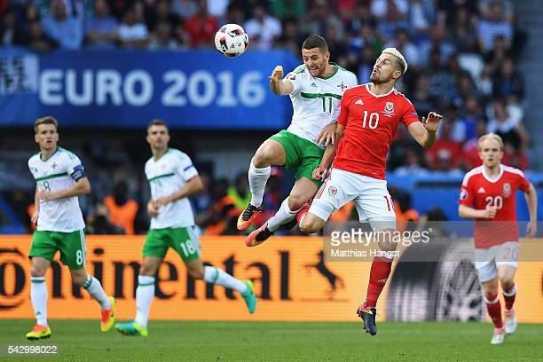 Conor Washington of Northern Ireland and Aaron Ramsey of Wales compete for the ball during the UEFA EURO 2016 round of 16 match between Wales and...