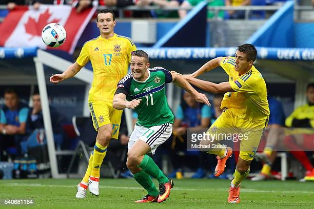 Conor Washington of Northern Ireland and Yevhen Khacheridi of Ukraine compete for the ball during the UEFA EURO 2016 Group C match between Ukraine...