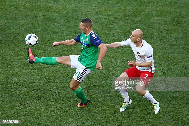 Conor Washington of Northern Ireland controls the ball under pressure of Michal Pazdan of Poland during the UEFA EURO 2016 Group C match between...