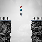 Conquering adversity creating a bridge to business partnership concept as a group of people on one cliff making an agreement with another using air balloons as a metaphor for bridging the gap for succ