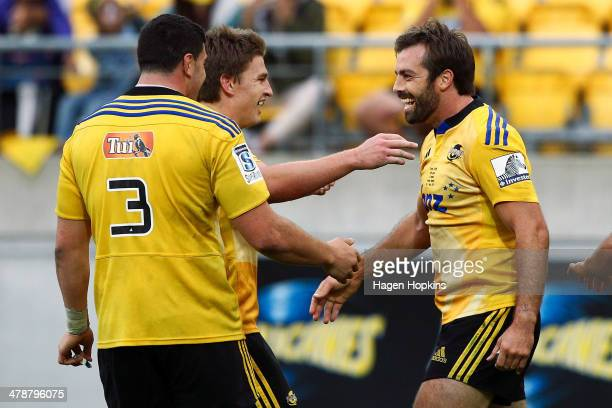 Conrad Smith of the Hurricanes is congratulated on his try by teammates Jeffery ToomagaAllen and Beauden Barrett during the round five Super Rugby...