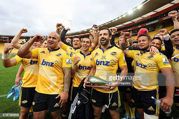 Conrad Smith of the Hurricanes poses with team members to celebrate his 100th Super Rugby game during the round five Super Rugby match between the...