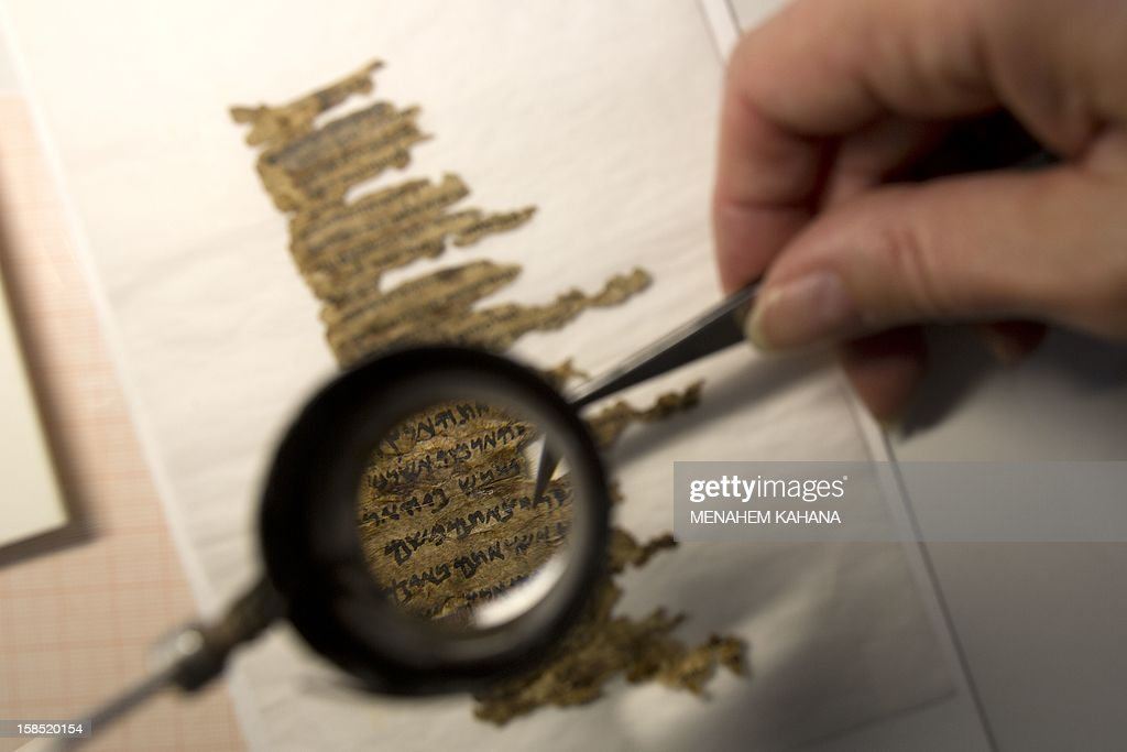 A conservation analyst from the Israeli Antiquities department examines fragments of the 2000-year-old Dead Sea scrolls at a laboratory in Jerusalem before photographing them on December 18, 2012. The director-general of the Israel Antiquities Authority Shuka Dorfmann and Professor Yossi Matias, managing director of Google Israel, announced the publishing of the Dead Sea Scrolls online, initiated by the Israel Antiquities Authority and Google.
