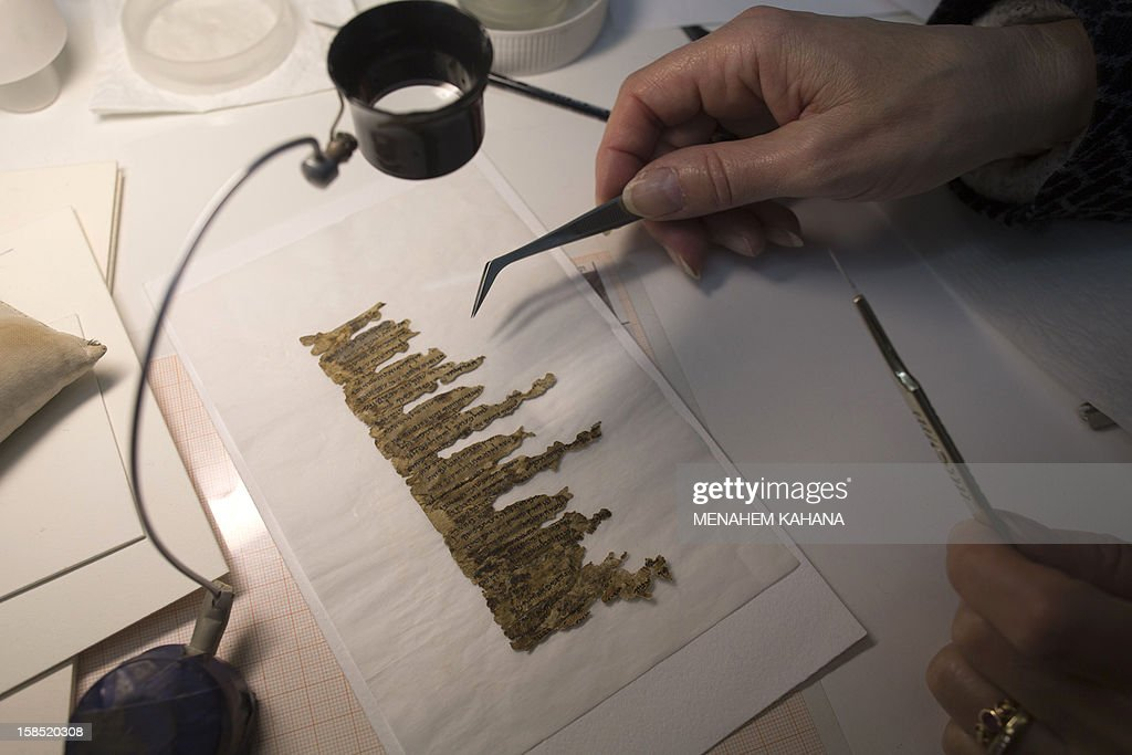 A conservation analyst from the Israeli Antiquities department examines fragments of the 2000-year-old Dead Sea scrolls at a laboratory in Jerusalem before photographing them on December 18, 2012. The director-general of the Israel Antiquities Authority Shuka Dorfmann and Professor Yossi Matias, managing director of Google Israel, announced the publishing of the Dead Sea Scrolls online, initiated by the Israel Antiquities Authority and Google. AFP PHOTO/MENAHEM KAHANA