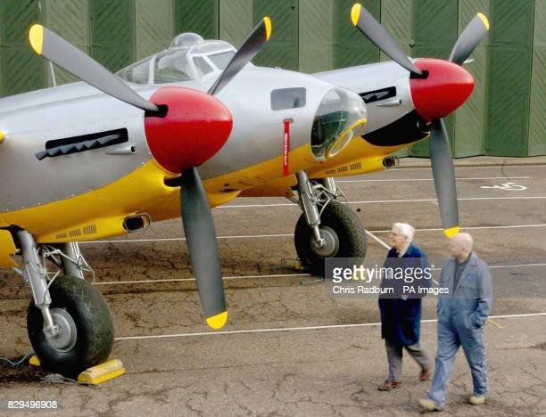 Conservationist Denis Hallisey and Roy Smith survey there work as they walk around the de Havilland Mosquito aircraft after a rollout ceremony