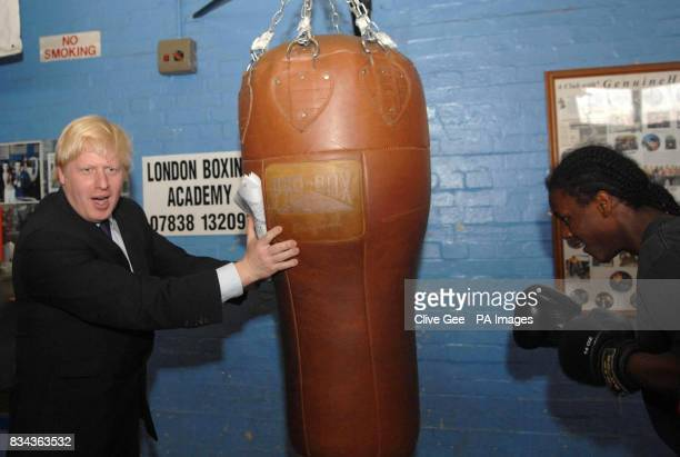 Conservative candidate for London Mayor Boris Johnson holds a punch bag for Chavez Campbell on a visit to the London Boxing Academy Community Project...