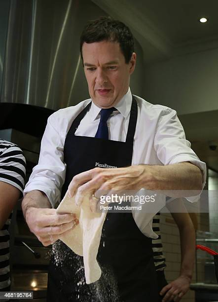 Conservative Chancellor George Osborne prepares a pizza as he visits a Pizza Express restaurant on March 31 2015 in Hove England Campaigning in what...