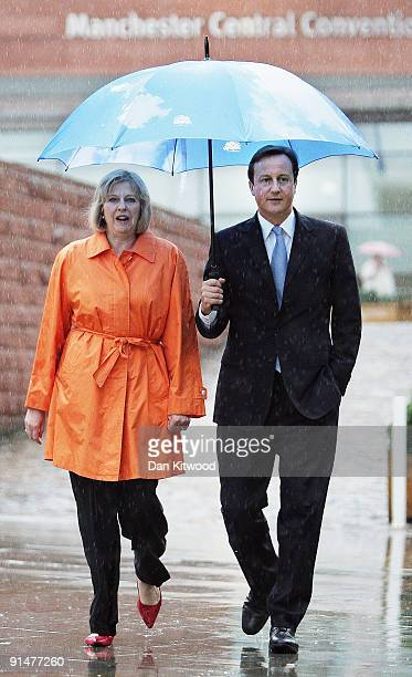 Conservative leader David Cameron and Shadow Secretary of State for Work and Pensions Theresa May walk through the rain on the second day of the...