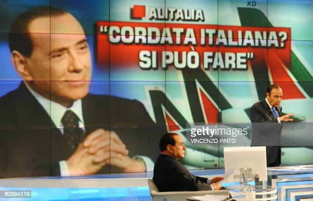 Conservative leader Silvio Berlusconi answers journalist's questions ahead of a giant screen showing an Alitalia plane during the broadcast 'Porta a...