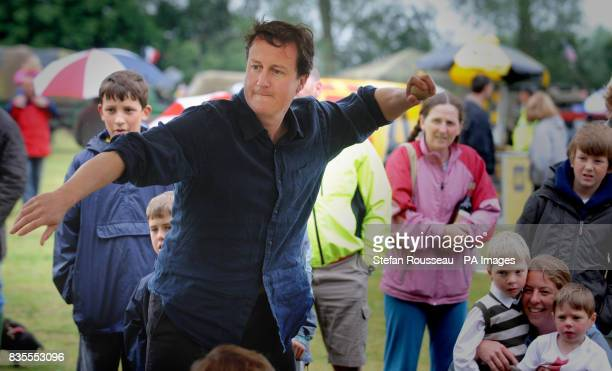 Conservative Party leader David Cameron has an attempt at the coconut shy after he officially opened the Aston Fete in Oxfordshire
