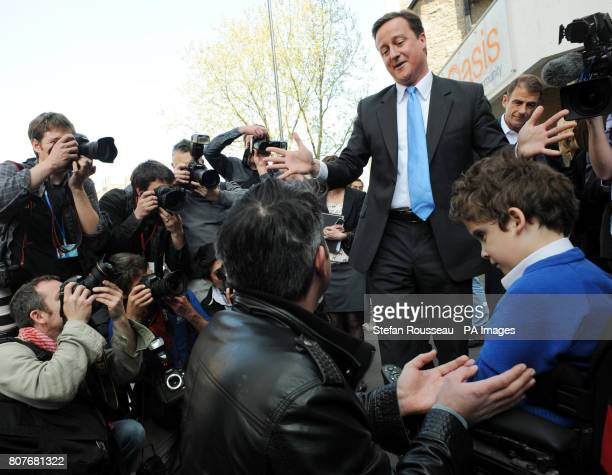 Conservative Party leader David Cameron speaks to Jonathan Bartley and his disabled son Samuel whilst in south London