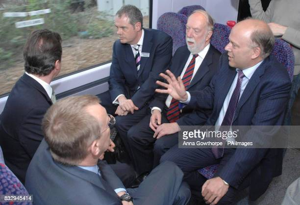 Conservative party Shadow transport Secretary Chris Grayling speaks to David Cameron and a group of transport and council officals during a journey...