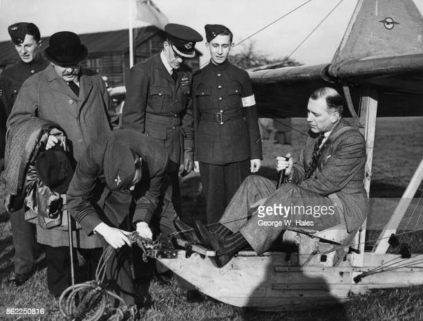Conservative politician Harold Balfour 1st Baron Balfour of Inchrye the UnderSecretary of State for Air is strapped into a glider during a visit to...