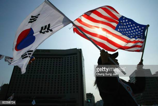 Conservative South Korean women holds a South Korean and US flag during the celebration of The March First Independence Movement Anniversary on March...