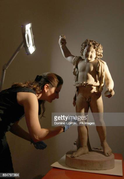 Conservator Amy Drago works to conserve a marble state of Bacchus as part of the Conservation in Focus exhibition at the British Museum in London