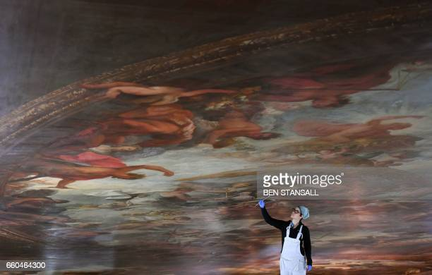 TOPSHOT A conservator poses during a photocall to promote the restoration project of the ceiling of the Painted Hall at the Old Royal Naval College...