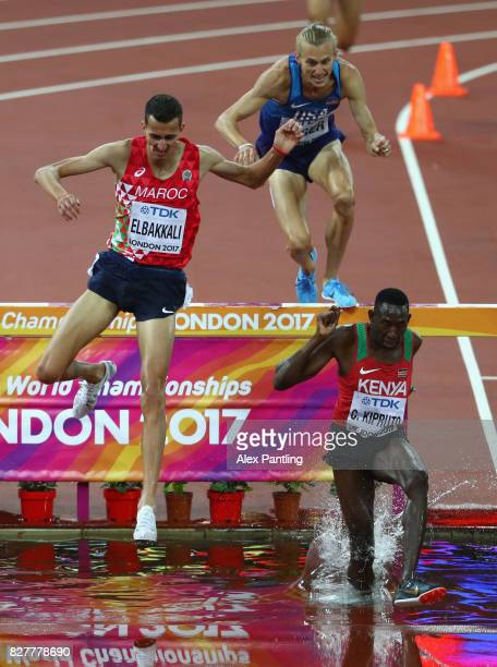 Conseslus Kipruto of Kenya leads from Soufiane Elbakkali of Morocco and Evan Jager of the United States as they clear the hurdle of the water jump...
