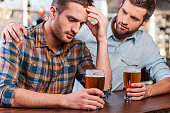 Depressed young man sitting at the bar counter and holding head in hand while being consoled by his friend sitting near him
