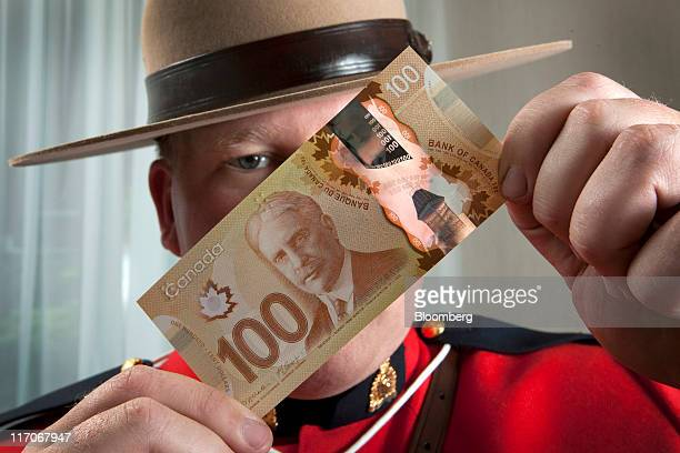 Constable Jeff Reid a counterfeit investigator for the Royal Canadian Mounted Police displays a $C100 Canadian bank note for a photograph in Toronto...