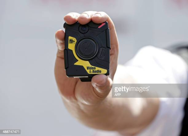 Constable Yasa Amerat poses for pictures with a bodyworn video camera at Kentish Town in London on May 6 2014 Police officers across London will wear...