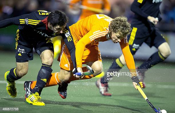 Constantijn Jonker of the Netherlands vies for the ball with Belg Loick of Belgium during an international field hockey match on the new field HV...