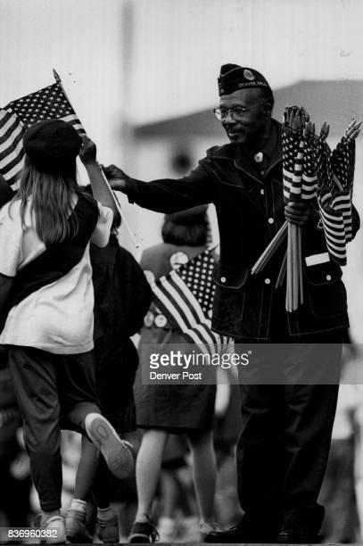 S Constitution Colo Celebration Seventyfiveyearold World War Two veteran George W Gray Jr of Denver an American Legion member hands flags to Girl...