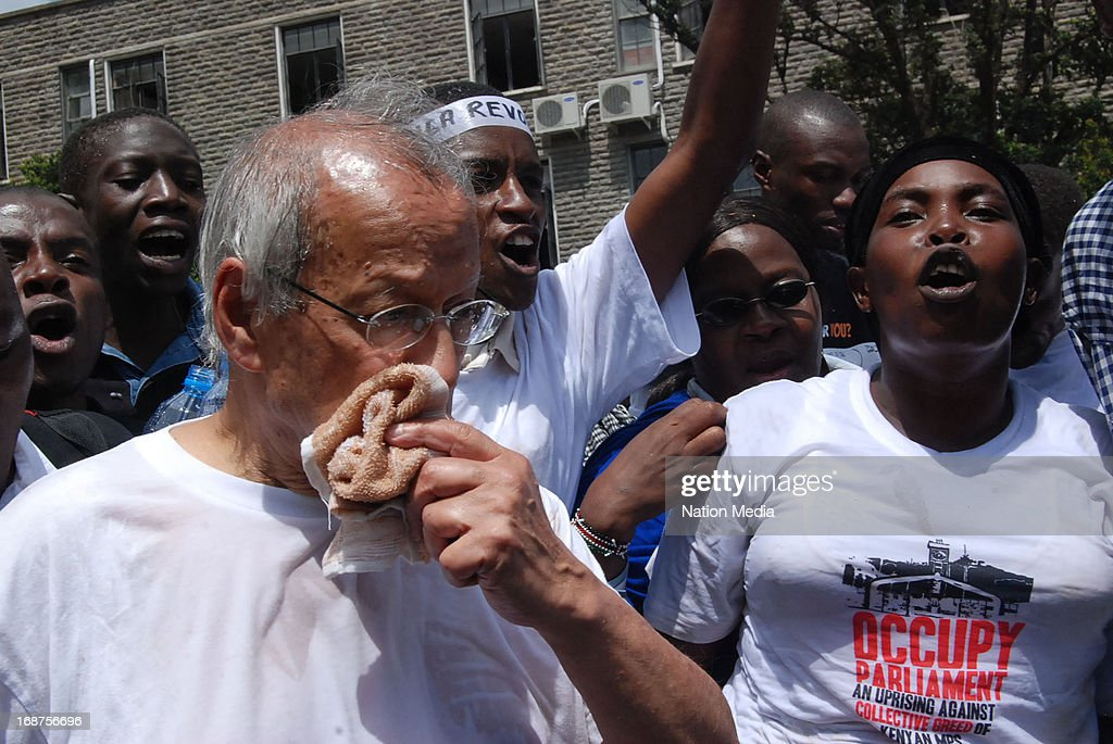 TANZANIA) Constitutional lawyer Yash Pal Ghai uses a handkerchief to avoid inhaling teargas during a pig protest on May 14, 2013 in Nairobi, Kenya. The protesters released a pig and about a dozen piglets outside parliament to show their anger at newly elected MPs demanding higher salaries. The protest was intended to portray the MPs as greedy.
